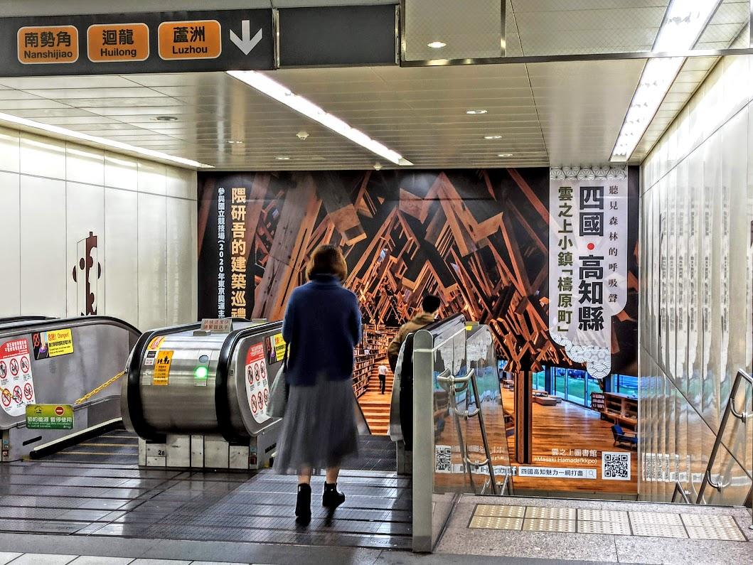 台北の地下鉄エスカレーターに乗る女性と壁面広告