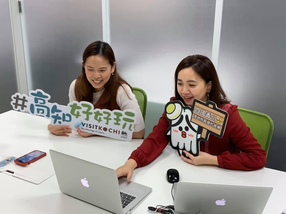 パソコンに向かいボードを掲げて通話する二人の女性
