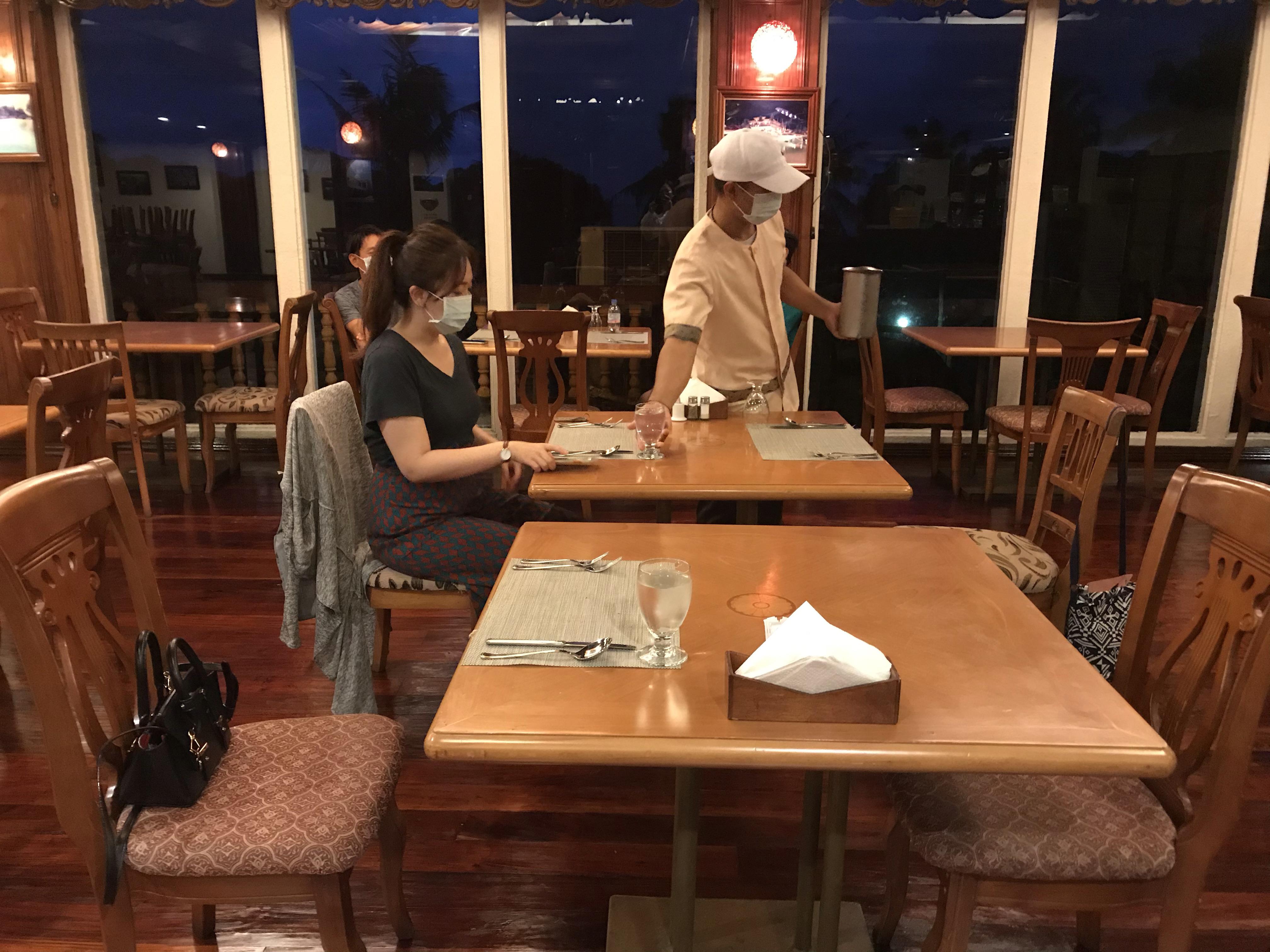 ホテル食堂にて食事を待つ女性