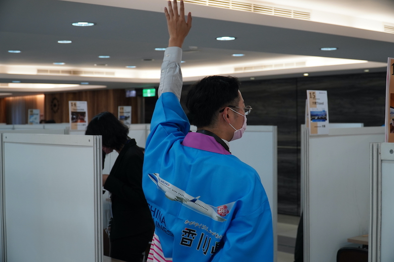 中華航空と香川県のハッピを着て手を挙げる男性
