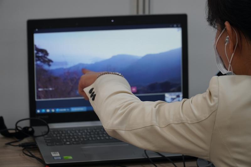 山の連なる景色を写したノートPCを指差す女性